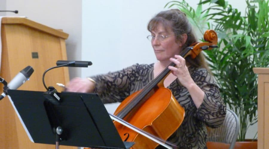 Marlene Moore playing her cello at an event.